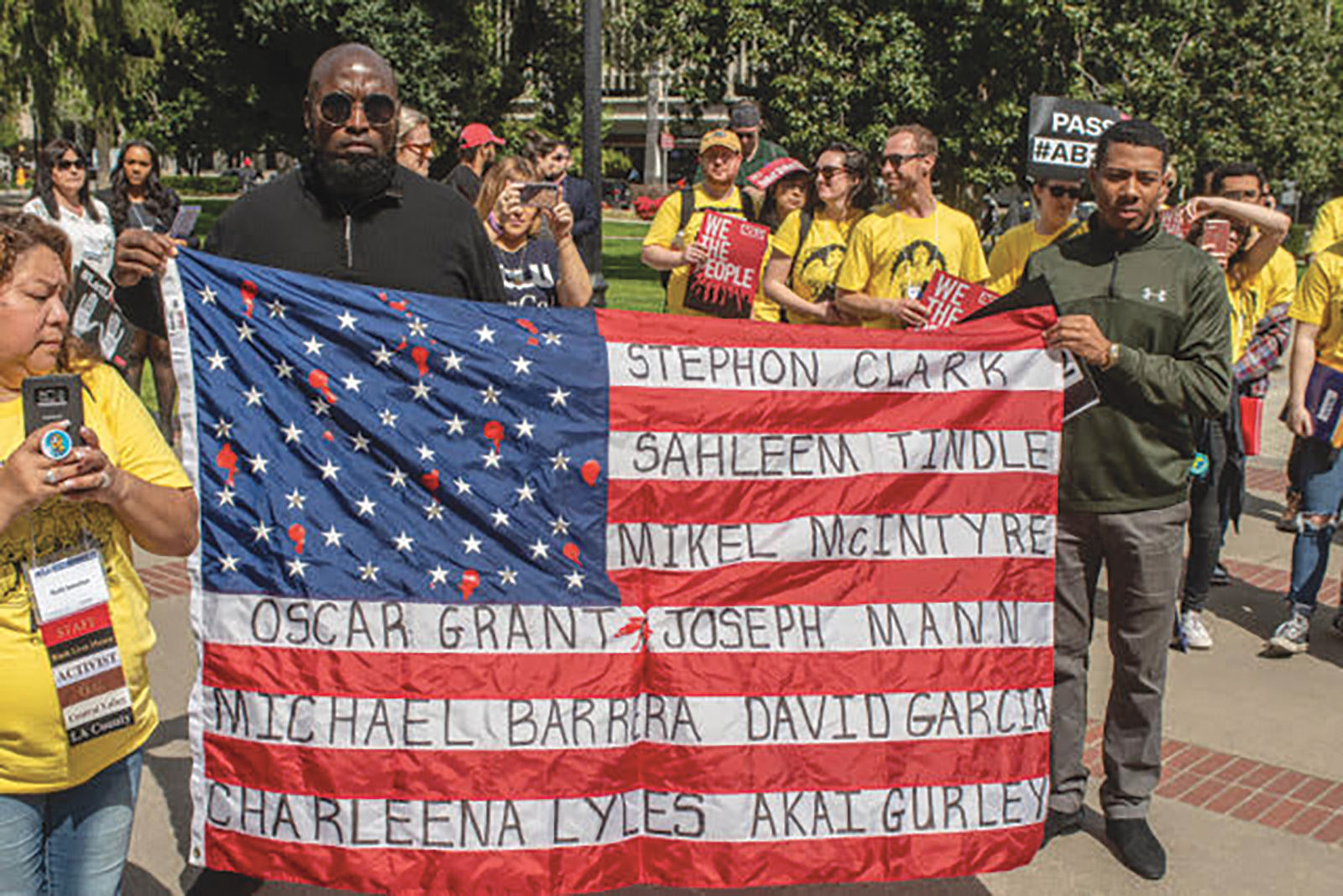 Malaki Seku Amen president of the California Urban Partnership with Khalil Ferguson at a rally at the State Capitol hold a flag with names of victims who were unarmed and killed by law enforcement. (Photo by Russell Stiger Jr.)