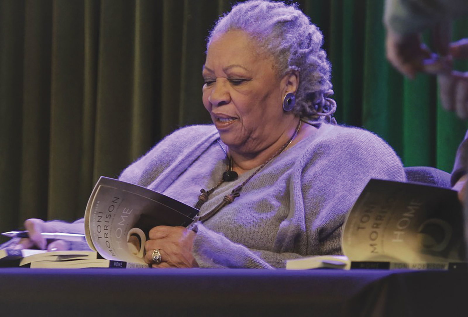"""FILE - In this Feb. 27, 2013 file photo, author Toni Morrison signs copies of her latest book """"Home,"""" during Google's online program series, Authors At Google, in New York. The Nobel Prize-winning author has died. Publisher Alfred A. Knopf says Morrison died Monday, Aug. 5, 2019 at Montefiore Medical Center in New York. She was 88. (AP Photo/Bebeto Matthews, File)"""