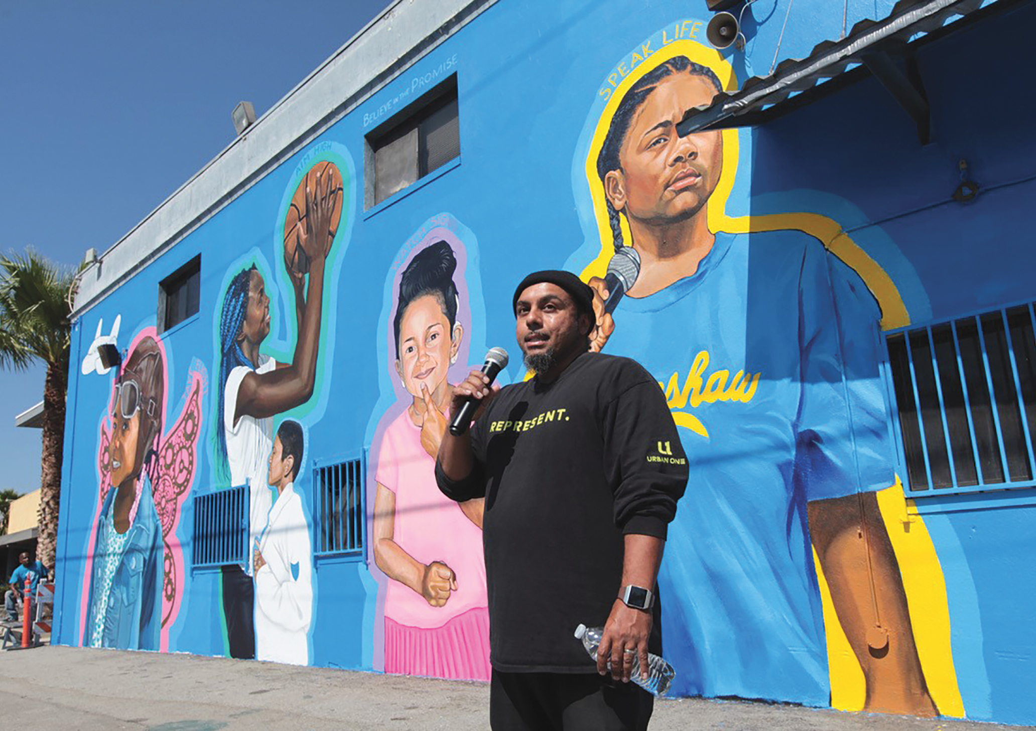 "Community artist Moses Ball speaks to the crowd at the unveiling of the ""Promise"" mural at the Boys & Girls Clubs Challengers Clubhouse in South Los Angeles. (Photo Credit: Greg Schneider)"