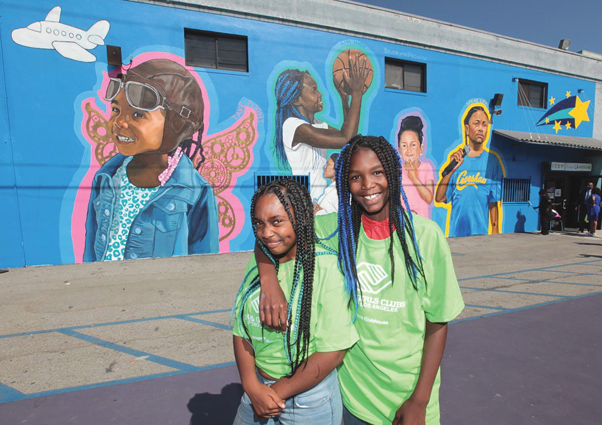 "Hasina (right), depicted in the mural holding the basketball, and Brailyn (left) stand in front of the new ""Promise"" mural at the Boys & Girls Clubs Challengers Clubhouse in South Los Angeles. (Photo Credit: Greg Schneider)"