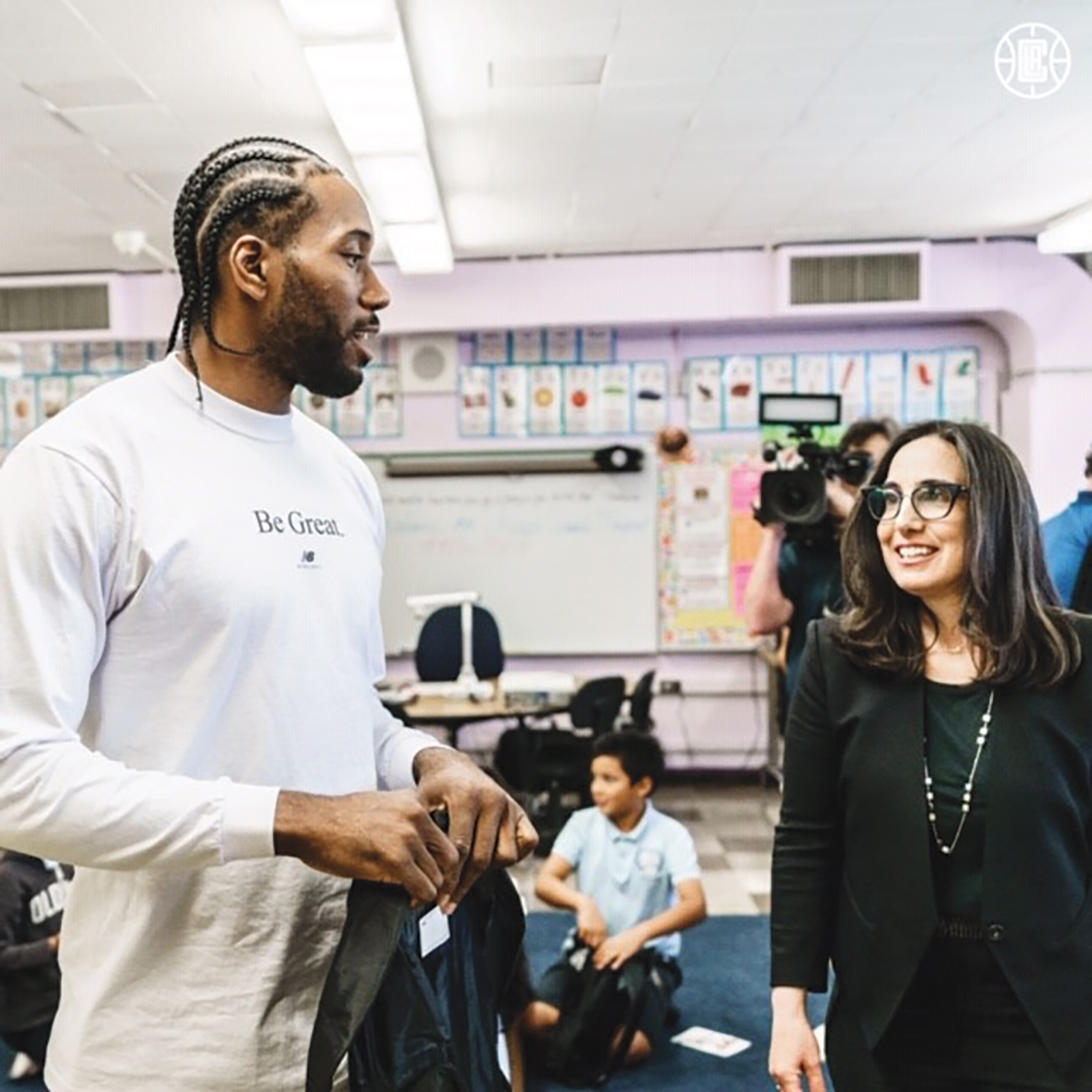 Kawhi and Gillian Zucker passing out Back Packs at 107th St. School (Photo Credit LA Clippers)