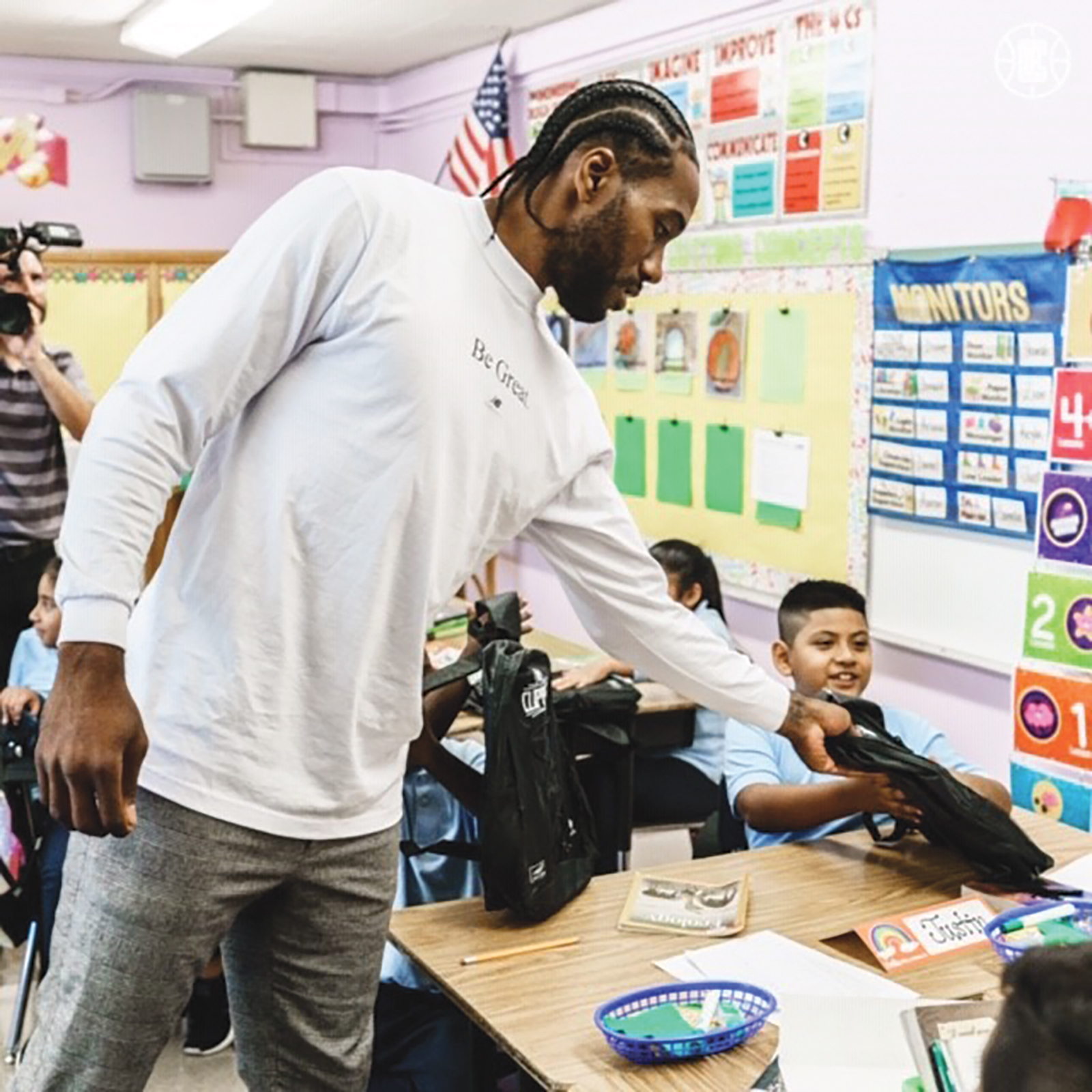 Kawhi Leonard passing out Back Packs at 107th St. School (Photo Credit LA Clippers)