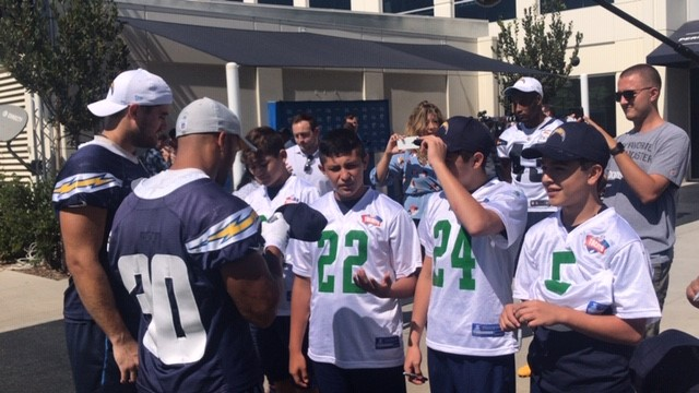 LA Chargers Austin Ekeler (#30) and Derek Watt give autographs to players on the Tochito's, the Mexican Flag Football Champions. (Courtesy Photo)