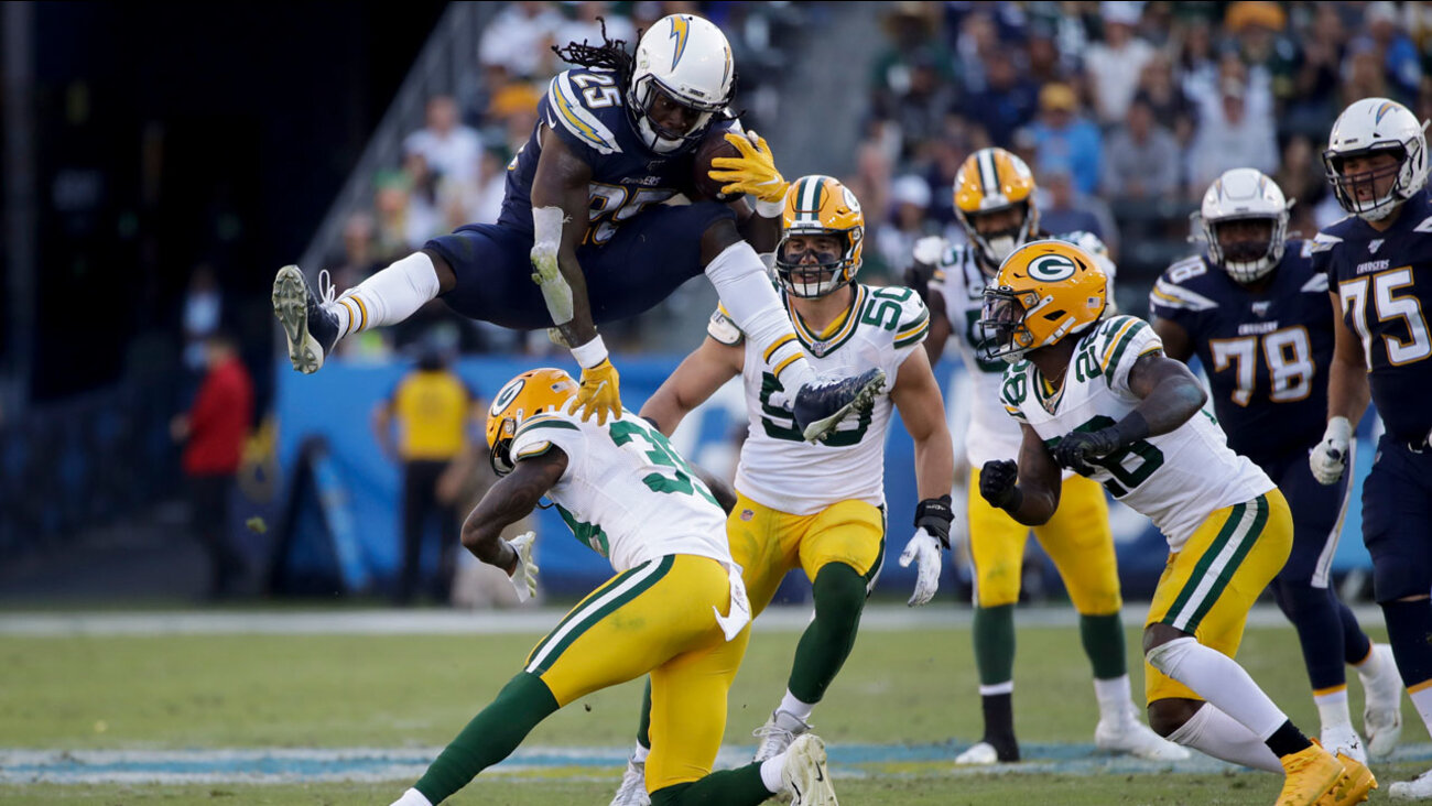 L.A. Chargers running back Melvin Gordon jumps over Green Bay Packers defensive back Chandon Sullivan during the second half of an NFL football game Sunday, Nov. 3 in Carson. (Marcio Jose Sanchez)