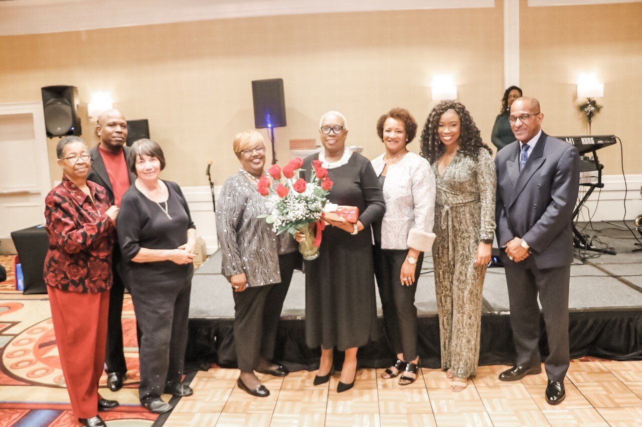 Tee Daniels (Center Left) and the board presenting Lilli J. Parker (Center Right) with flowers and a gift. (Carrington Prichett photo credit)