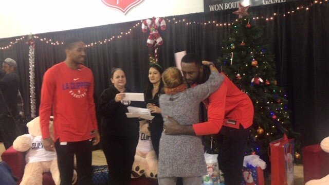 Grateful mother hugs Clippers Patrick Patterson after receiving Christmas gift during event. (Cam Buford Photo)