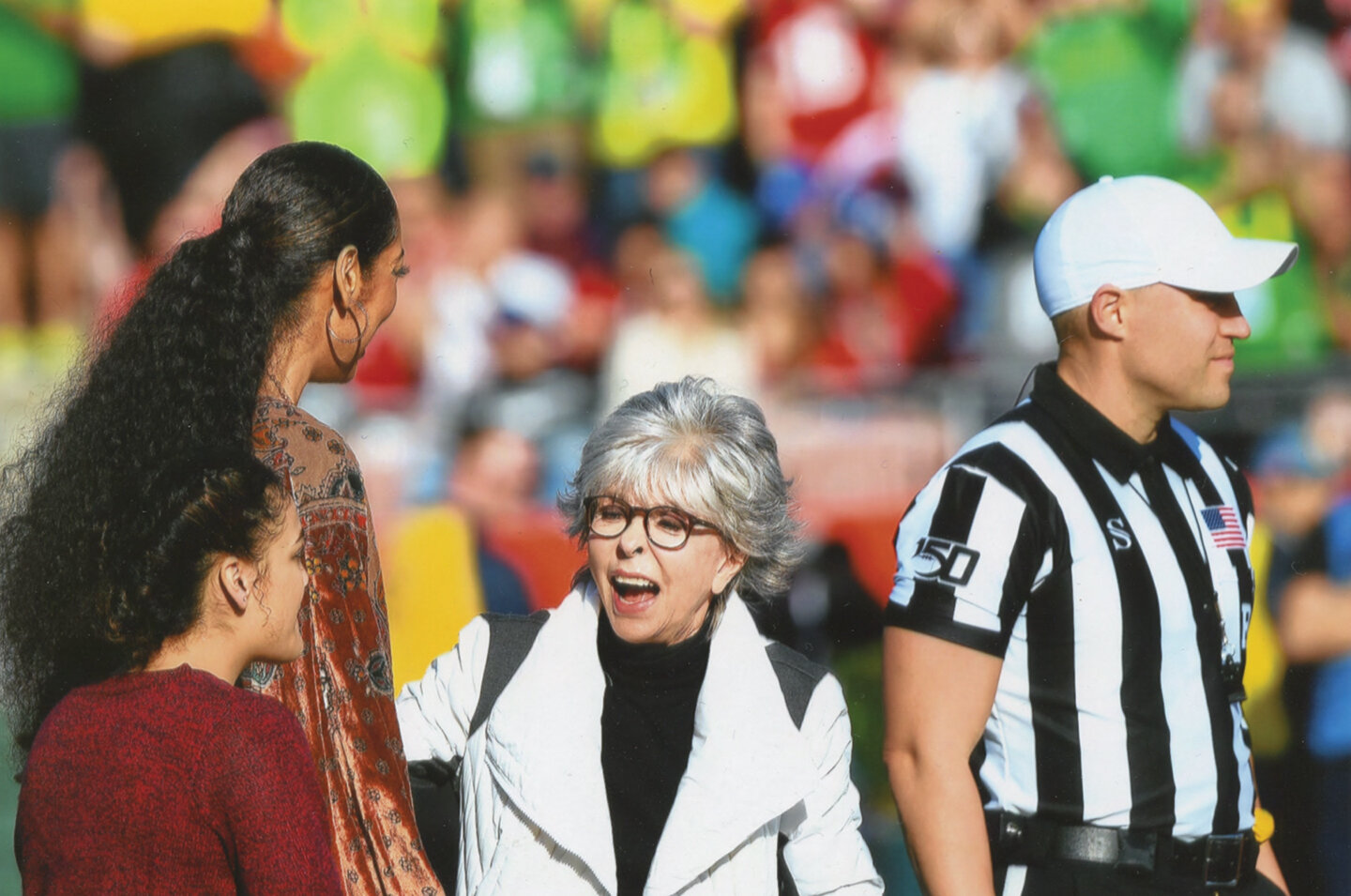 During the Pre-Game, Big-12 Referee Brandon Cruse (R) is joined at midfield by Grand Marshals (L to R) Laurie Hernandez, Gina Torres, and Rita Moreno who did the coin flip. (Earl Heath Photo)