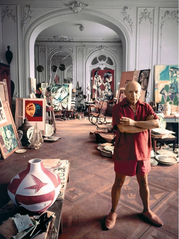Pablo Picasso photographed in his studio near Cannes, France in 1956. The Thonet rocking chair in the distance appears in many of his paintings. | Source:  The New York Times