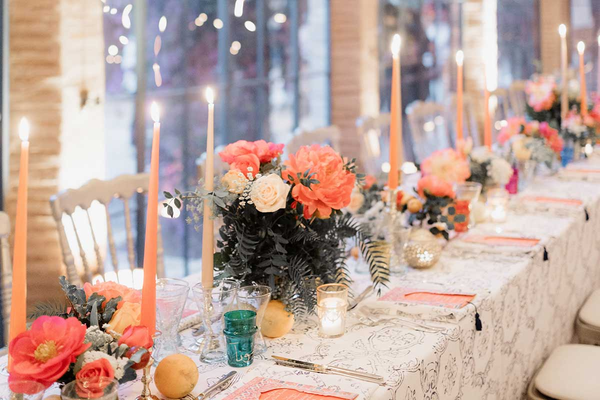 Moroccan style wedding dinner table set up with orange flowers and candles