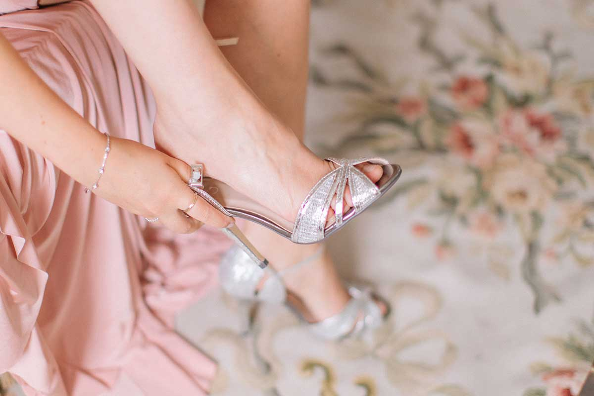 Bridesmaid putting on silver heels