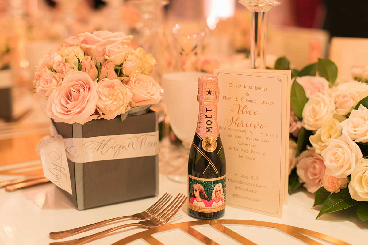 Table setting with Moet & Chandon bottle and pink roses in black square vase