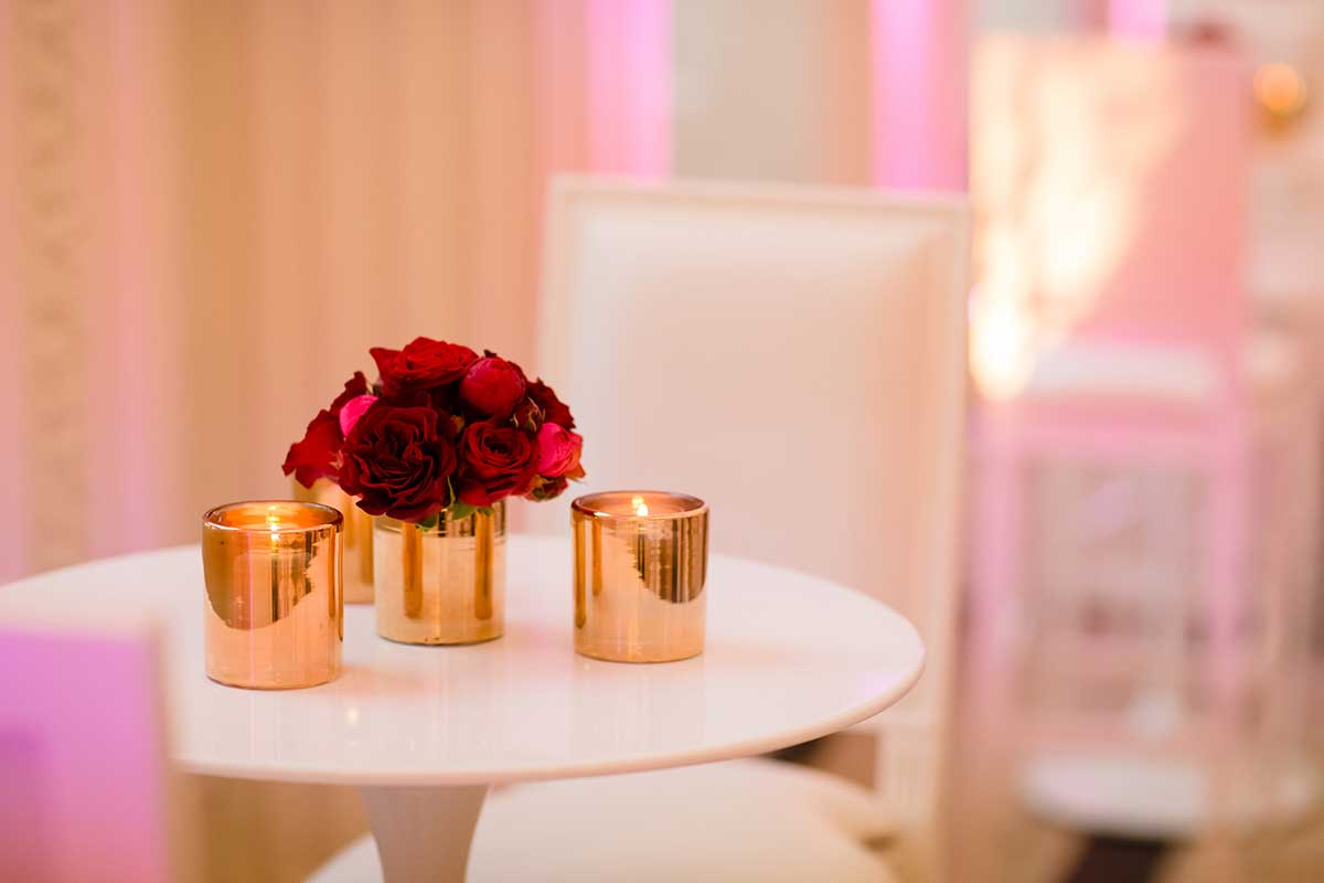 Red roses in gold vase and gold candle holders