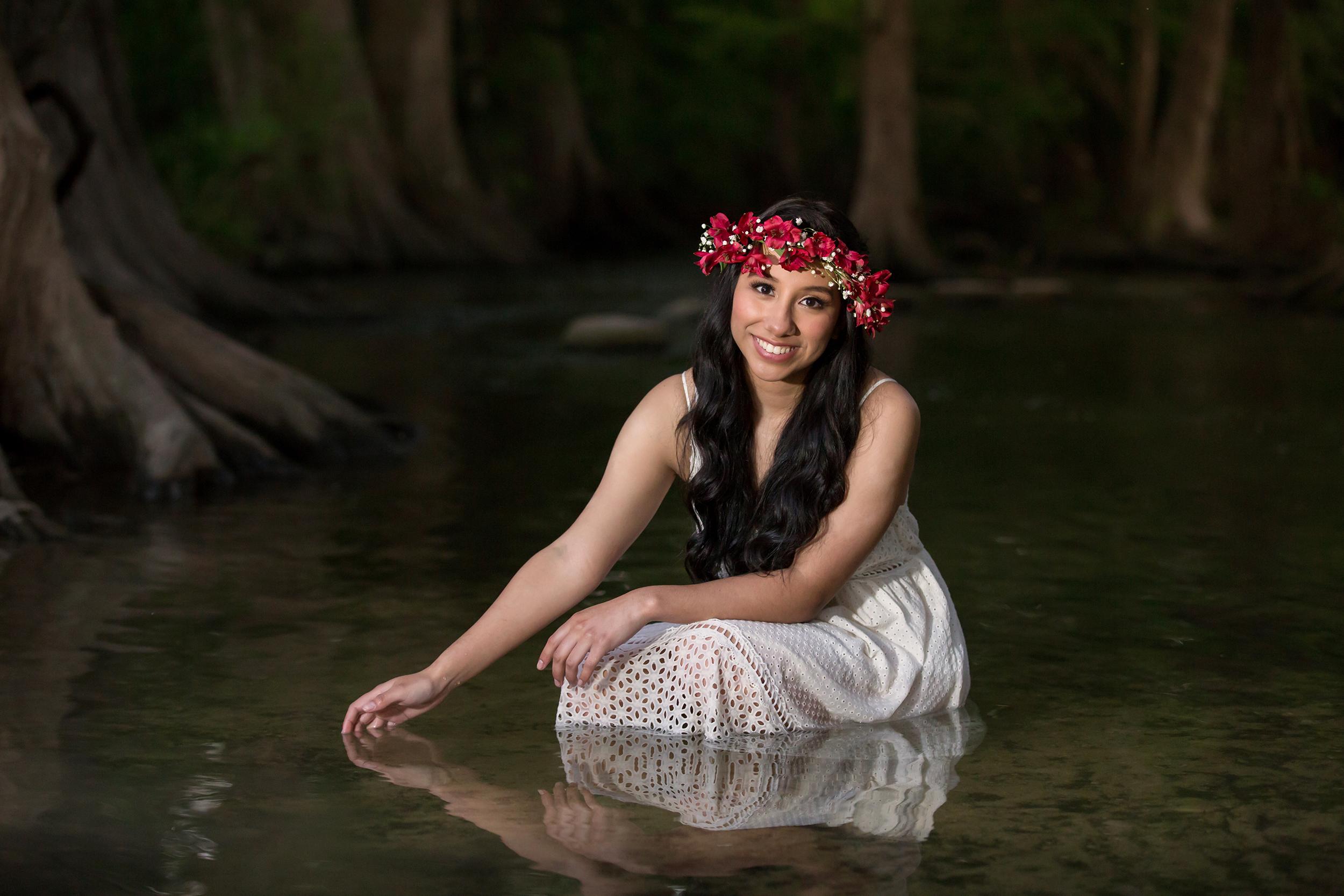 Senior-girl-flower-crown-white-dress-sitting-river.jpg