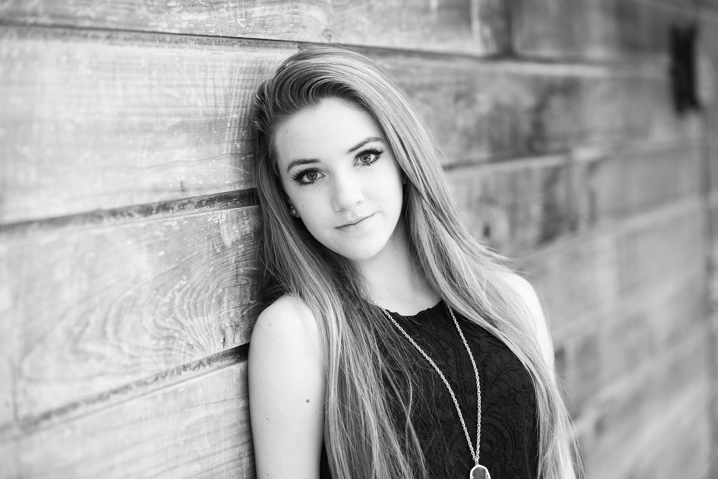 Teen-girl-bw-leaning-wood-wall.jpg