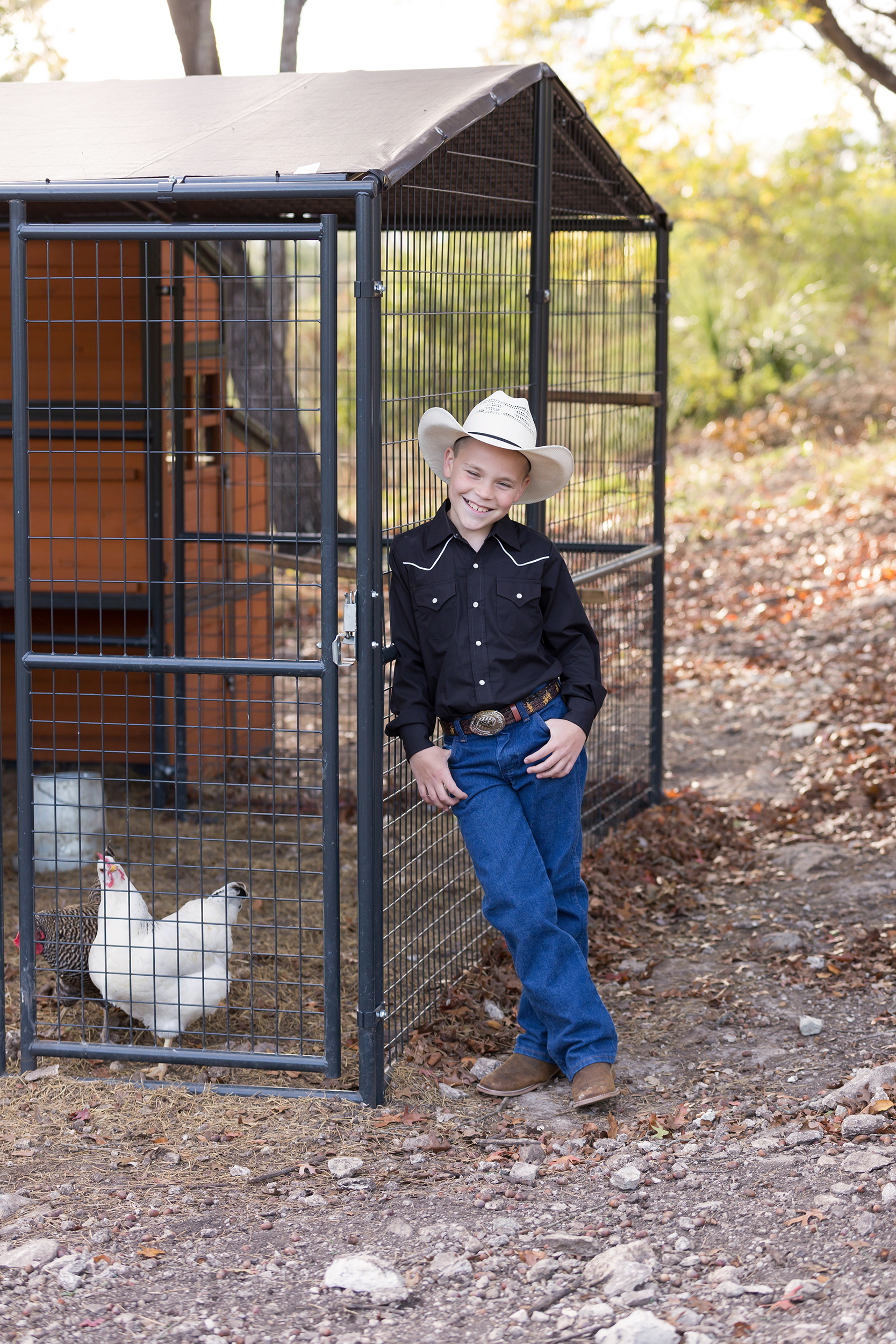Boy-western-hat-leaning-chicken-coop.jpg