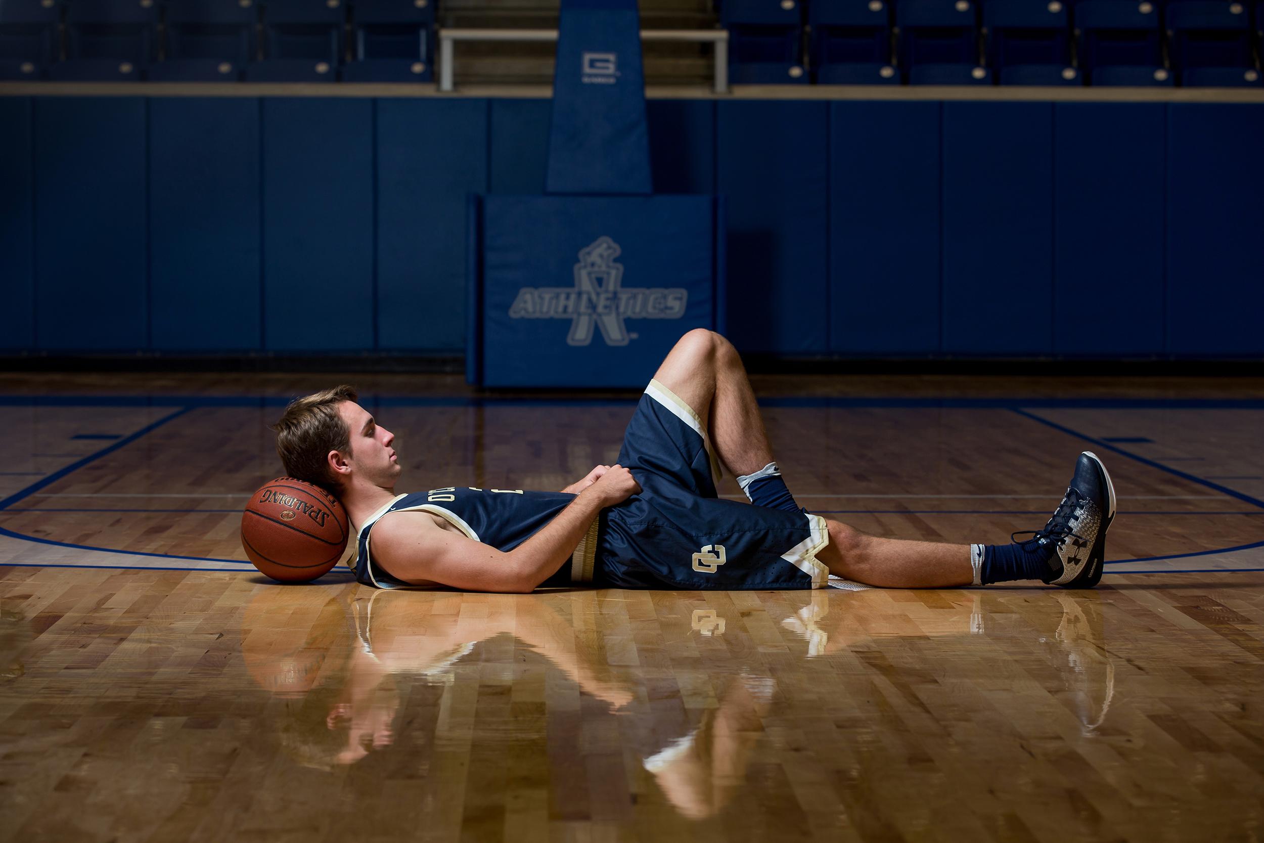 Senior-boy-basketball-laying-reflection-court.jpg