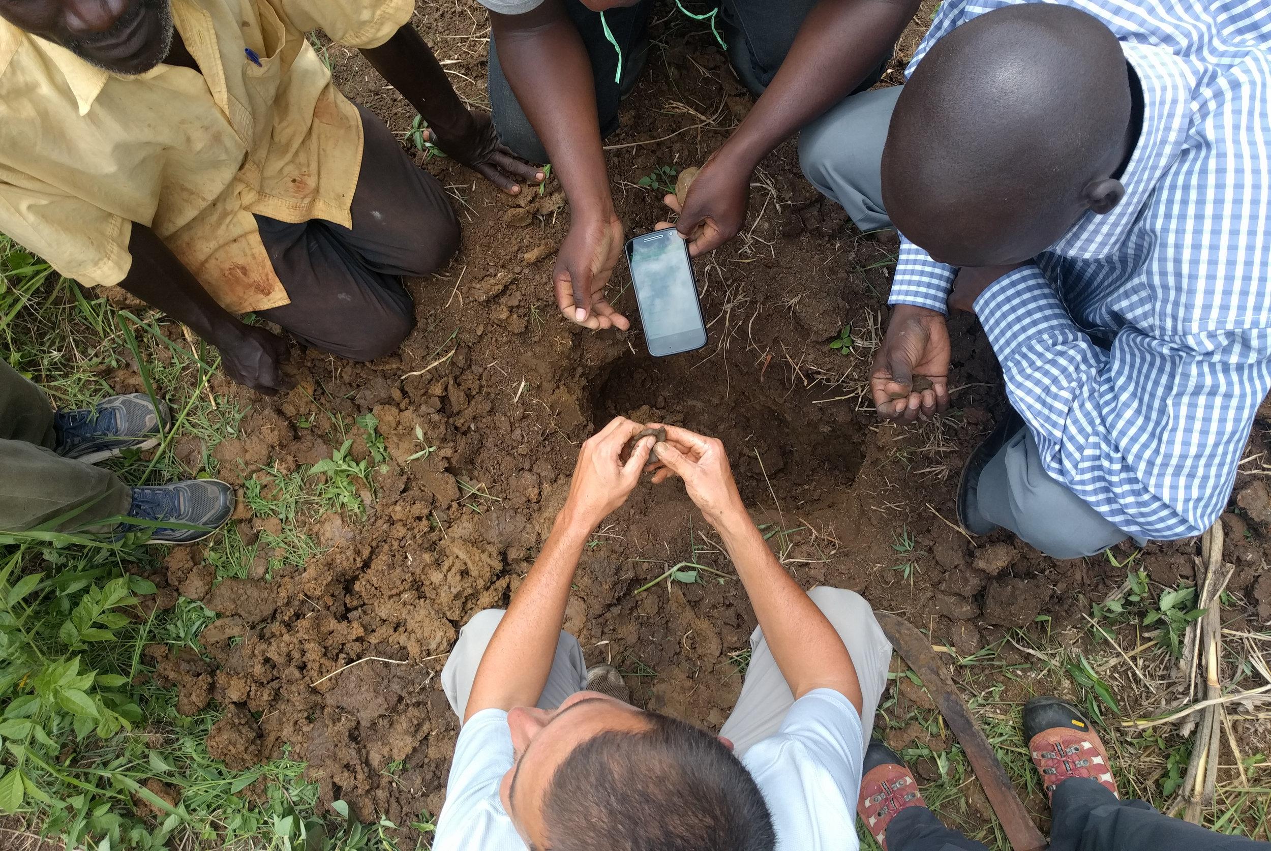 HIP team members exploring soil characterization with farmers at Kyekidde using a smartphone-based analysis app