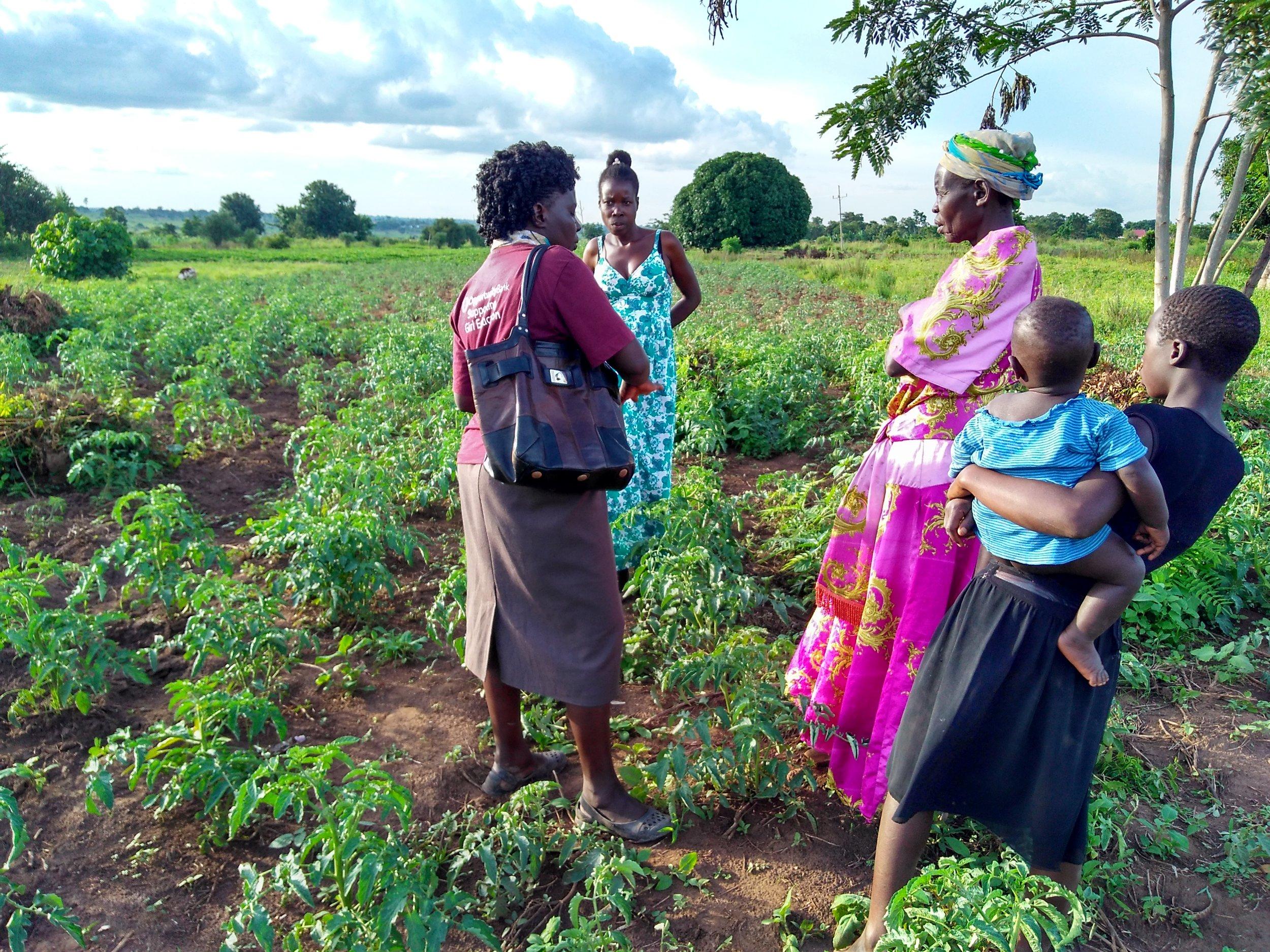 Helen Acuku (left) speaks with farmers at Aloet.
