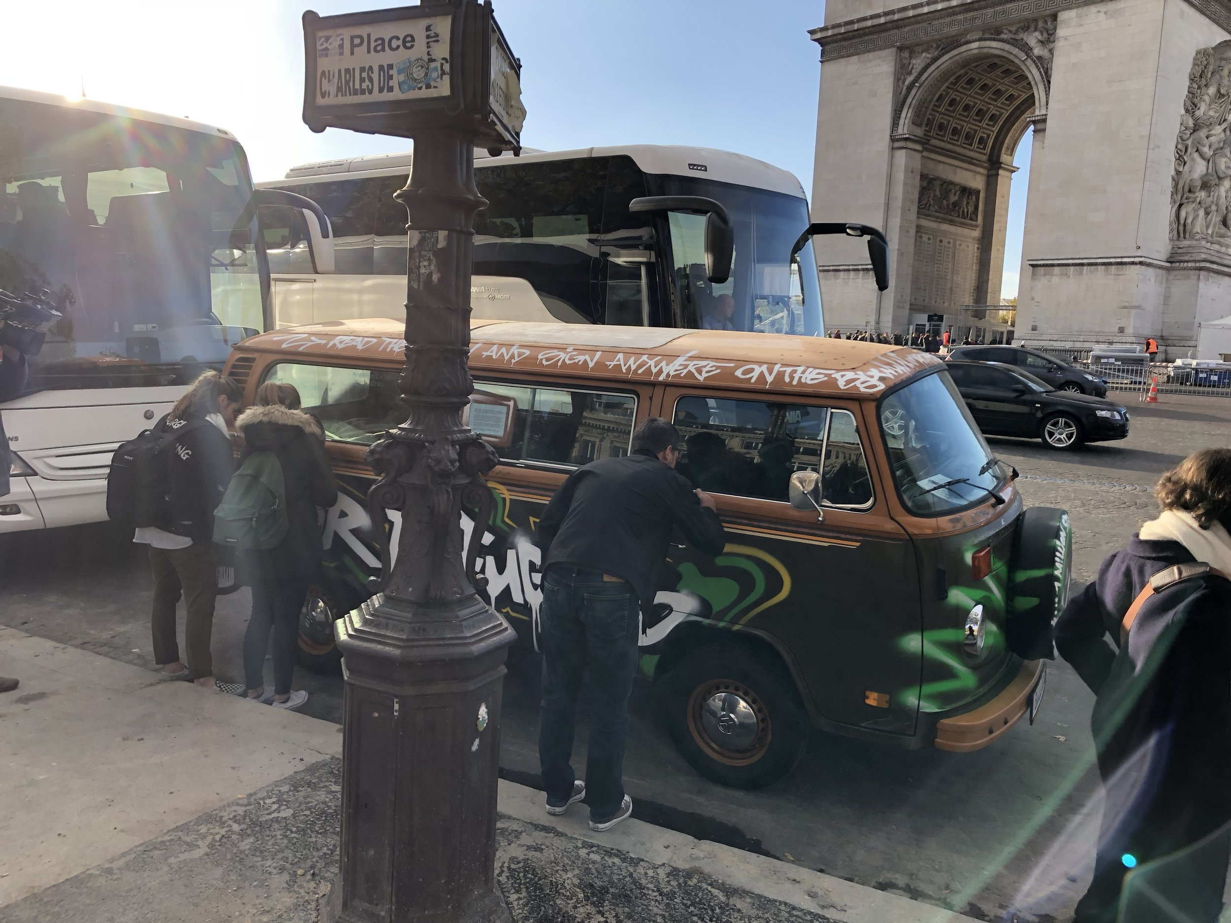 People signing vw bus outside arc de triomphe2.JPG