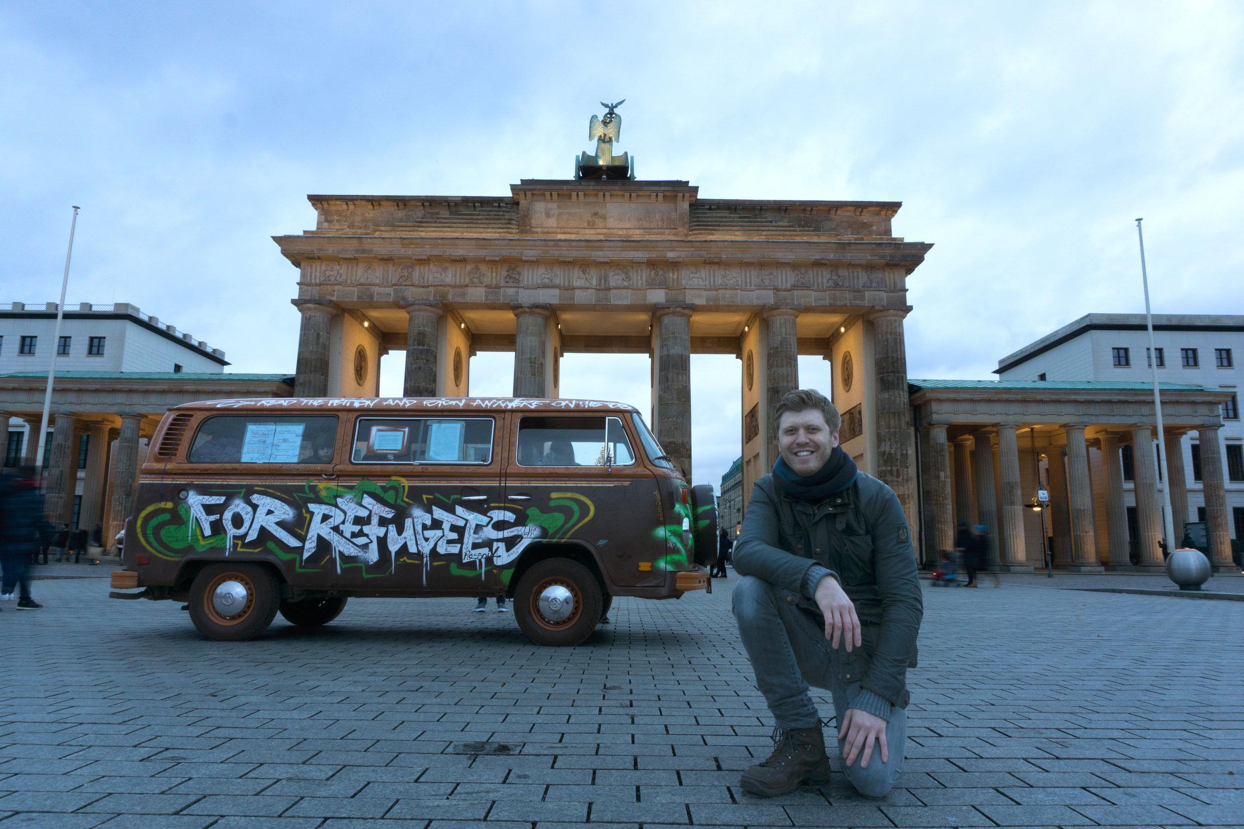Grigorij Richters kniet vor dem Brandenburger Tor. Hinter Ihm sein 45 Jahre alter VW Bus Bulli. 9. Dezember. Bild: Uwe Praetel