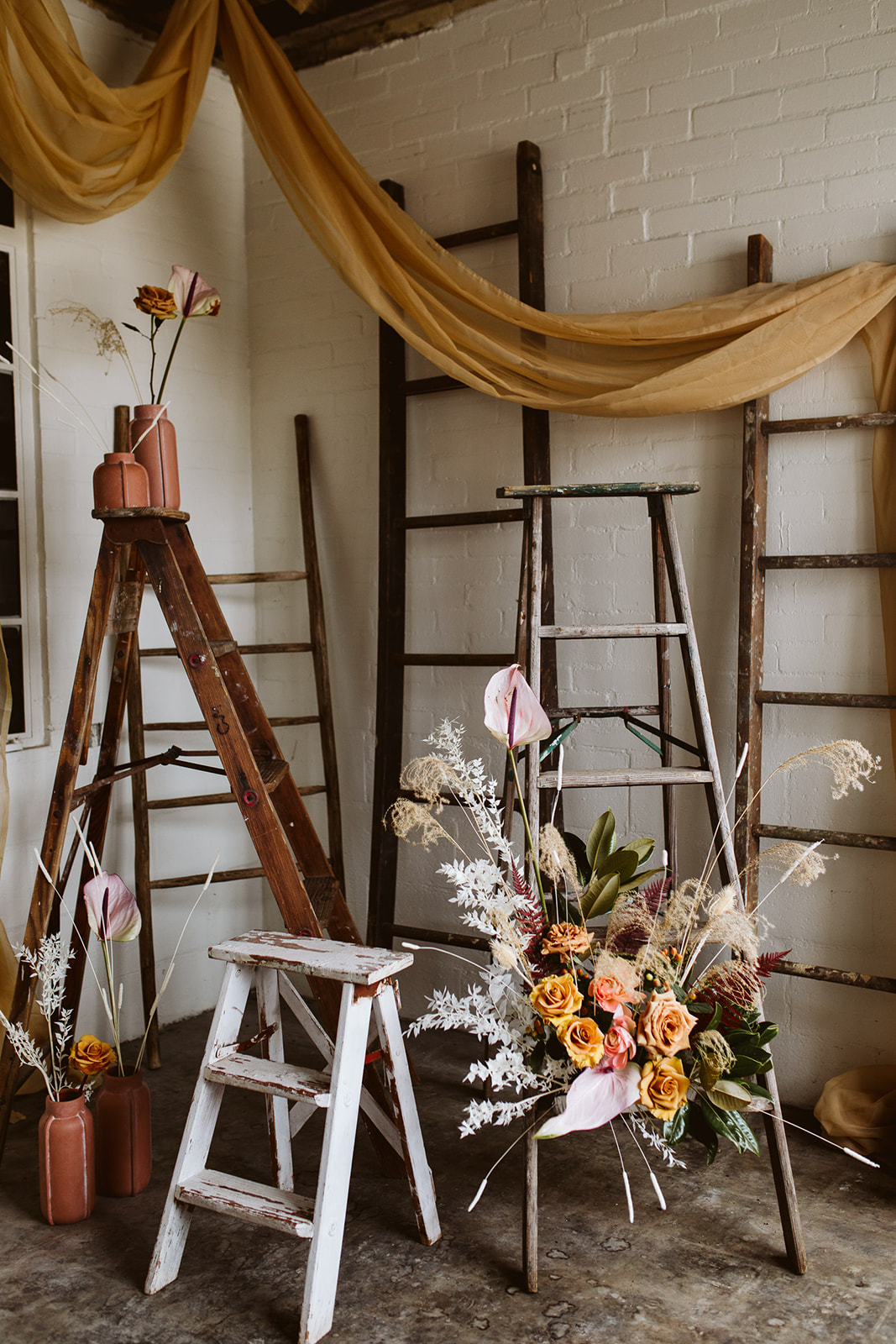 styled wedding shoot. wedding decor. ladder decor. boho wedding. eclectic wedding. unique decor. unique wedding decor. elopement decor. bright airy wedding. natural and wood accents. boho bouquet. beautiful details. vintage ladders. whimsical. whimsical bouquet.