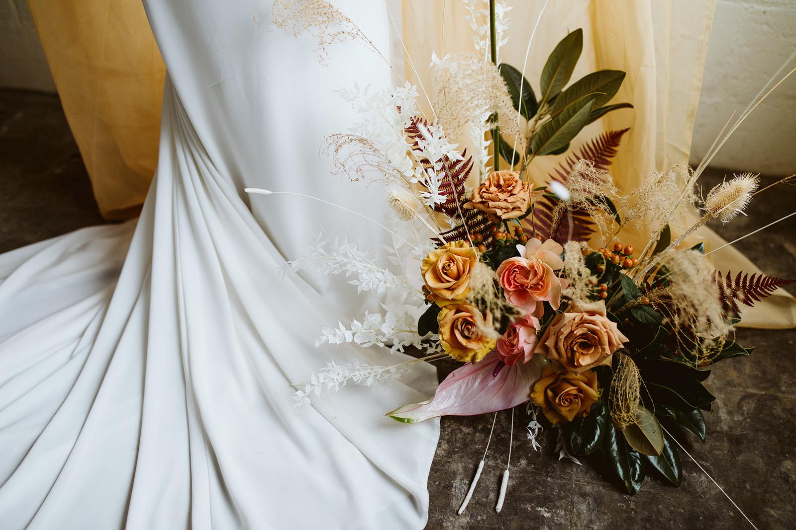 train details. wedding bouquet. elopement bouquet. unique florals. stunning wedding. adventurous bouquet. satin wedding gown. simple wedding gown. wildflowers and roses. stunning wedding dress. magical bouquet.