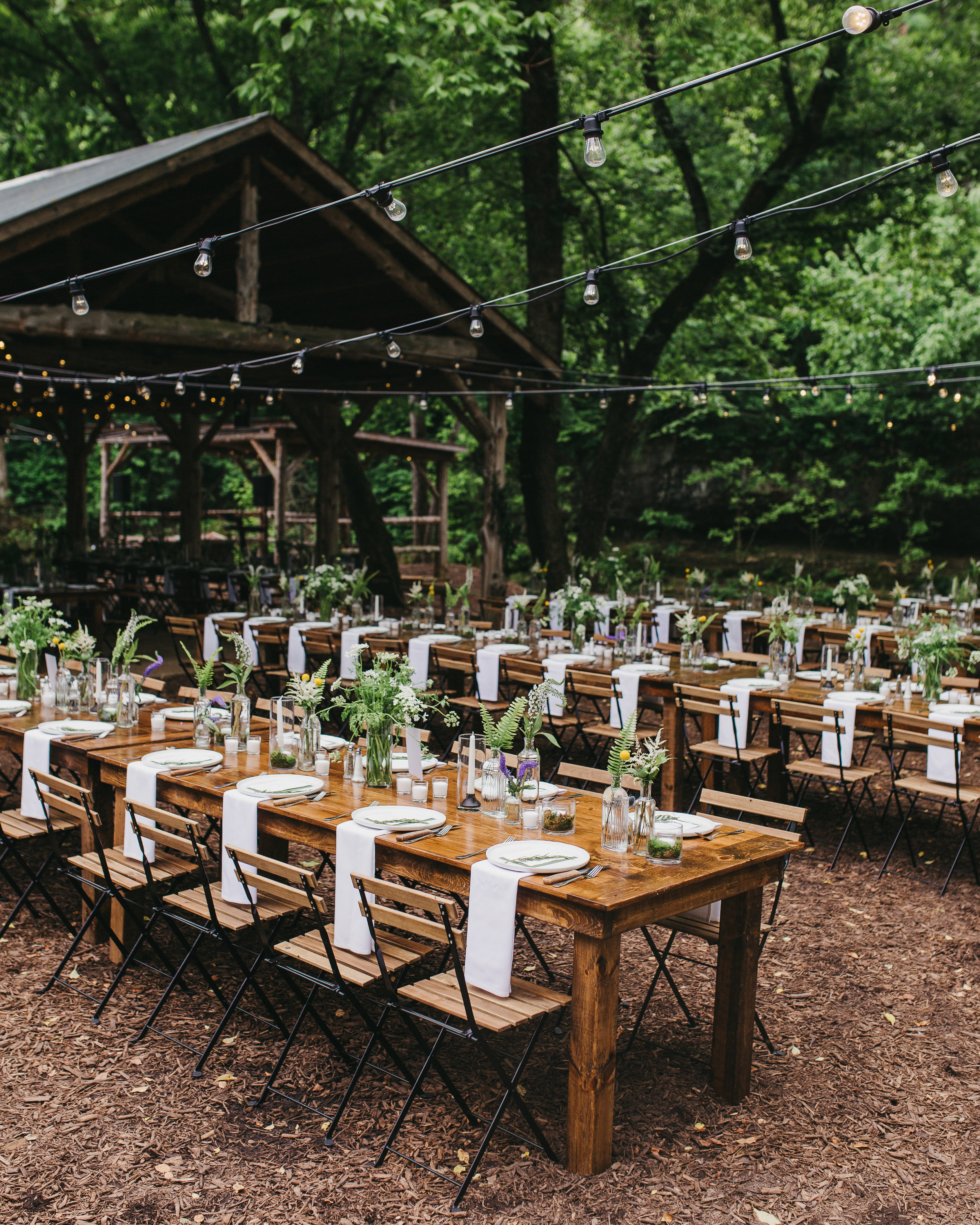 long farmhouse tables with greenery budvases at destination wedding