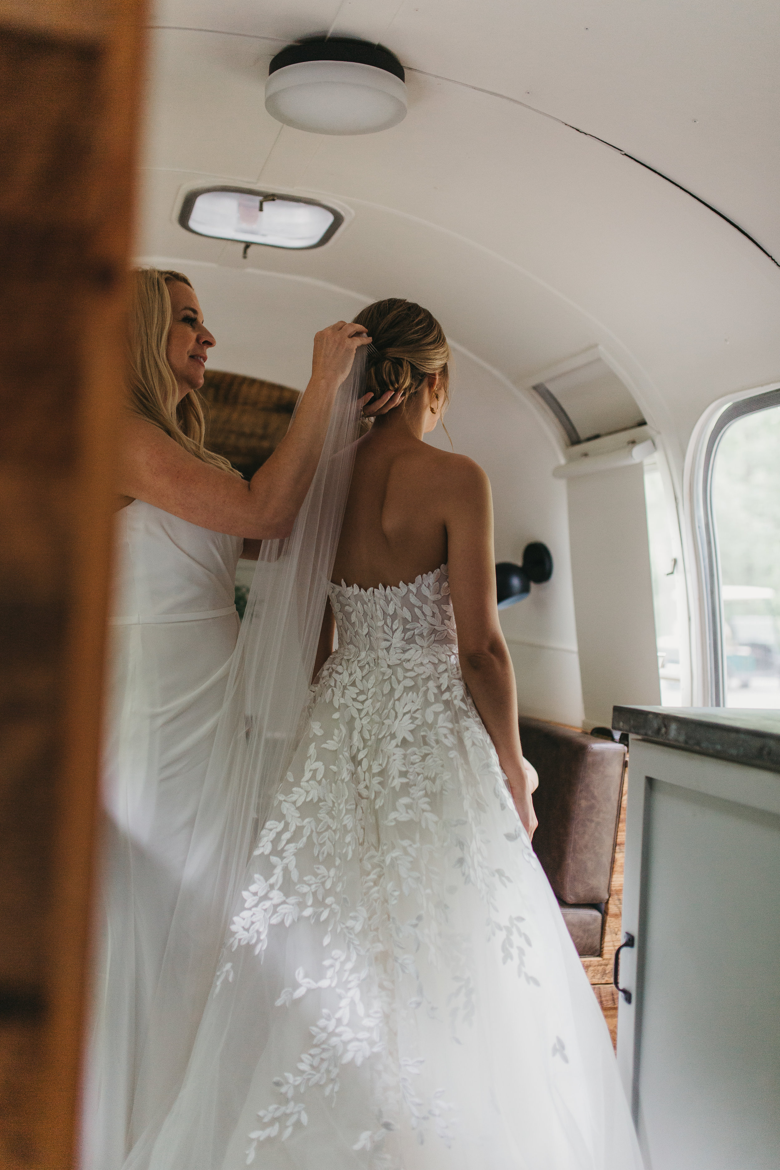 bride getting ready in airstream camper for wedding