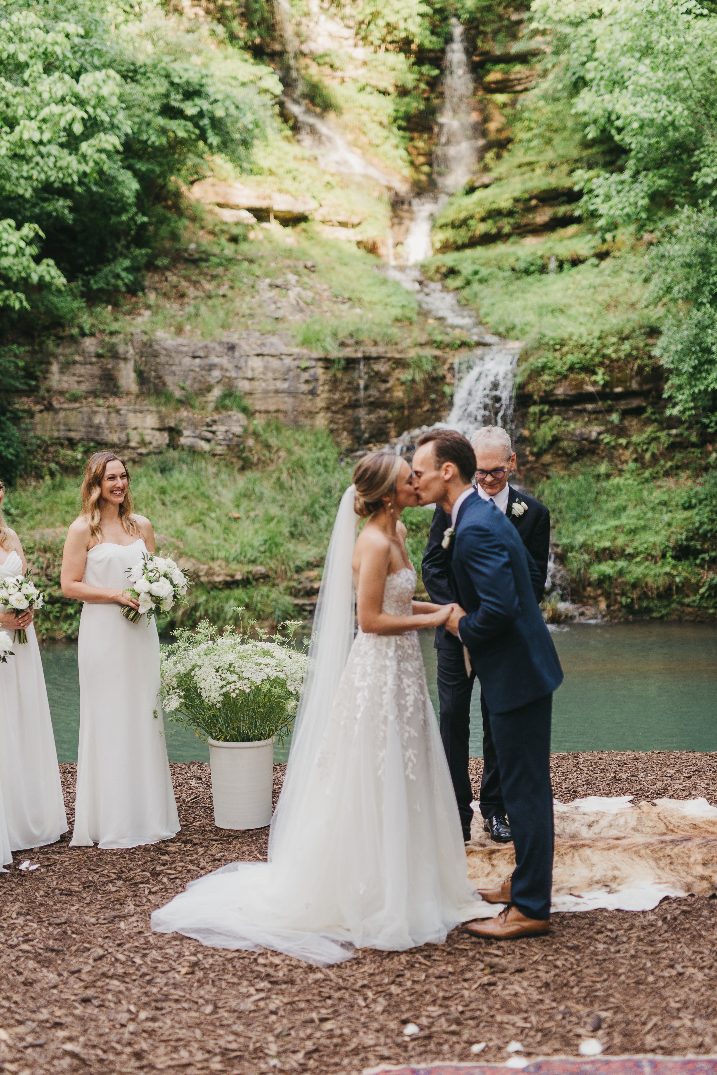 waterfall ceremony backdrop for wedding with hide rugs and greenery crocks