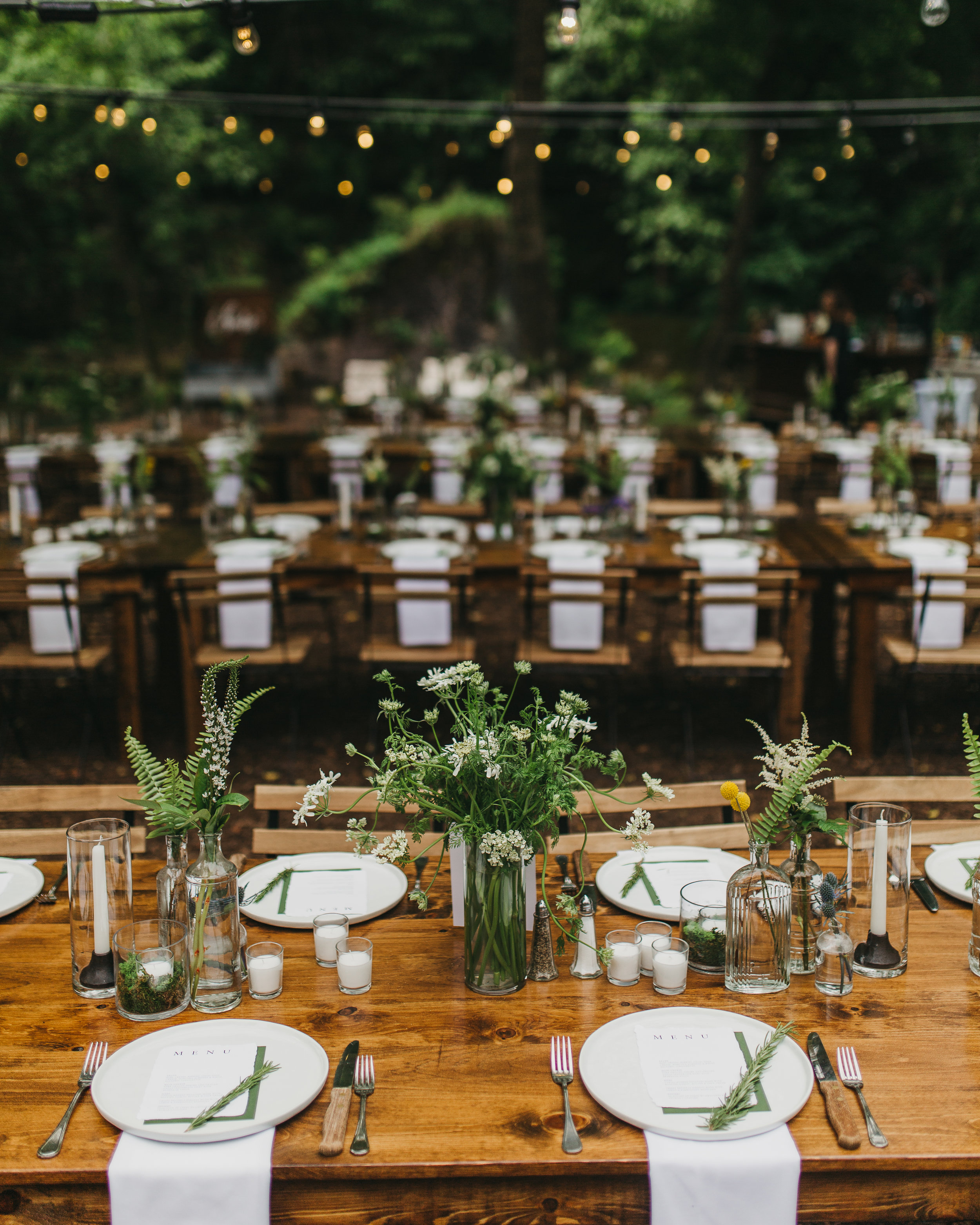 wedding farmhouse tables with greenery and budvases