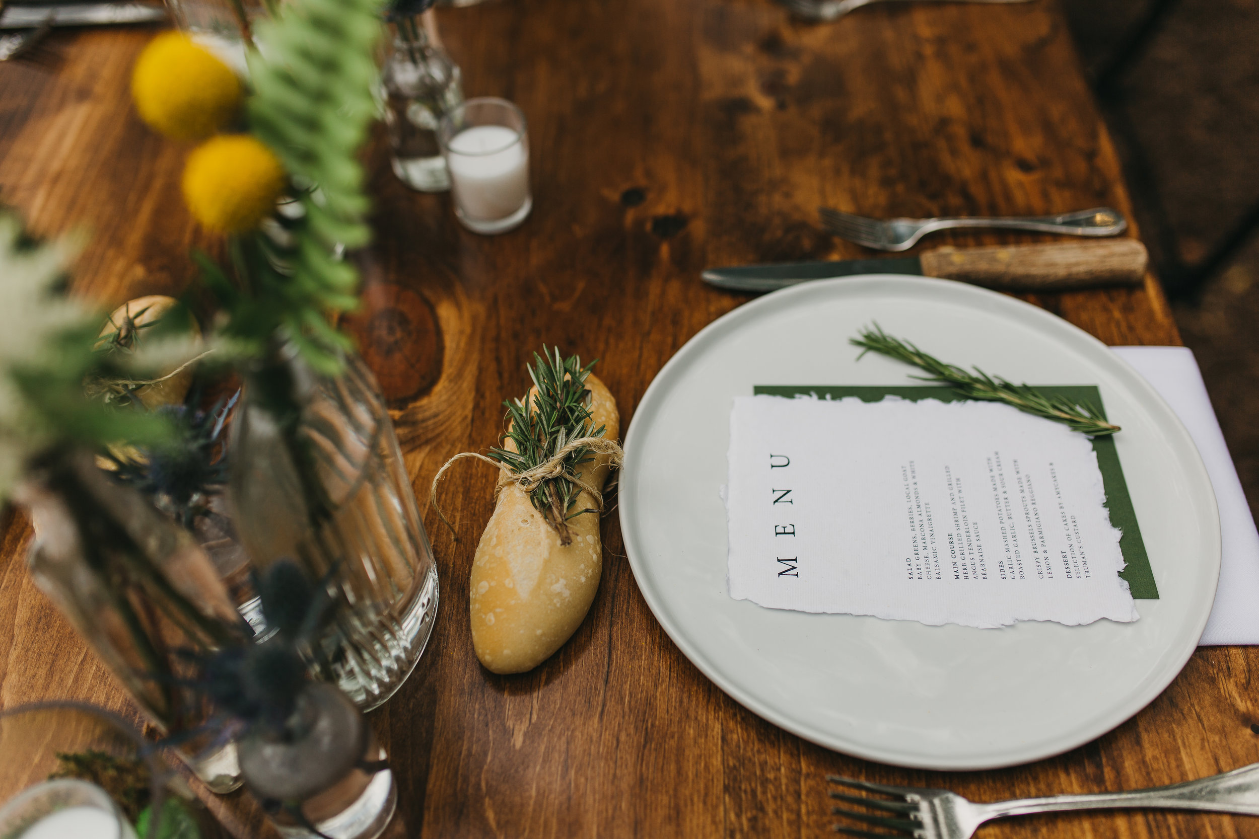 wrapped bread with rosemary on wedding place setting