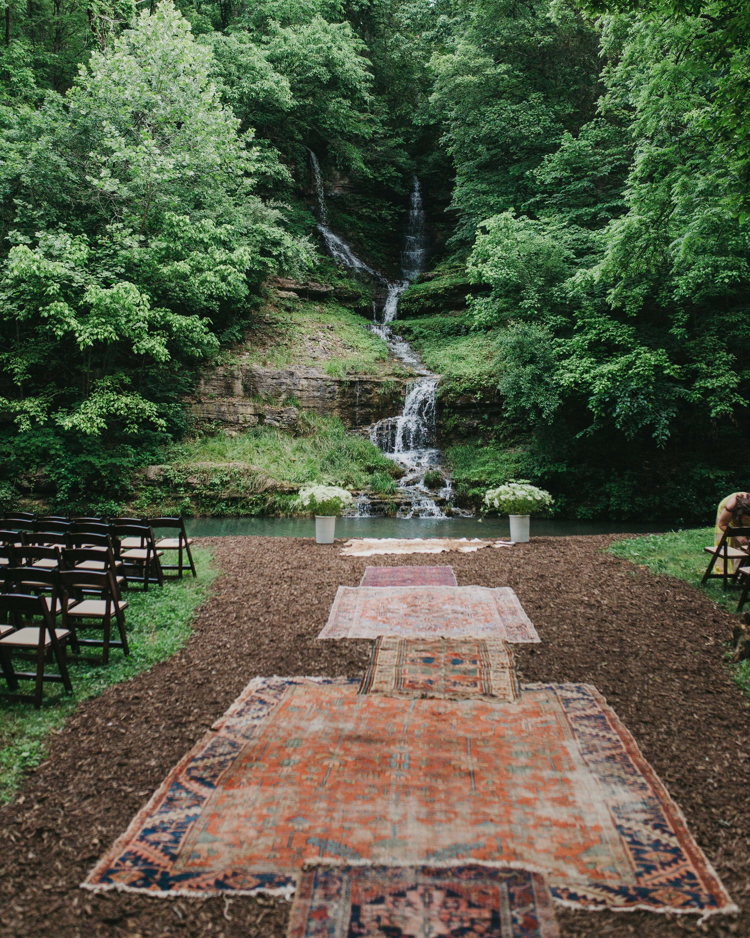 waterfall ceremony backdrop with vintage rugs lining aisle