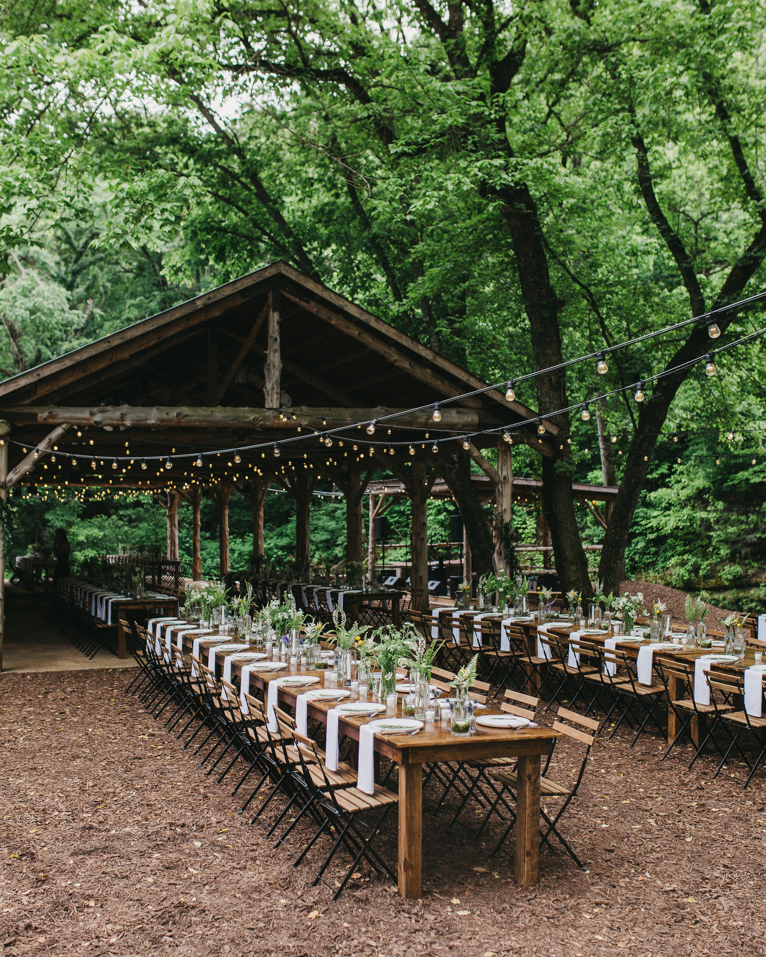 farmhouse tables with greenery and budvases at outdoor destination wedding
