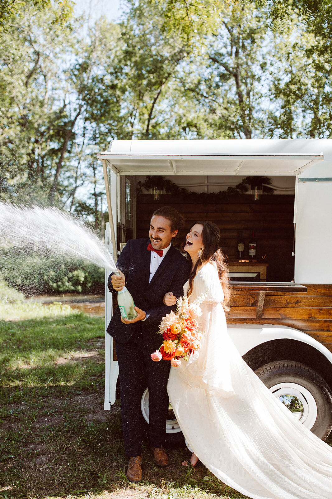 wedding couple popping bottle of champagne at trailer bar