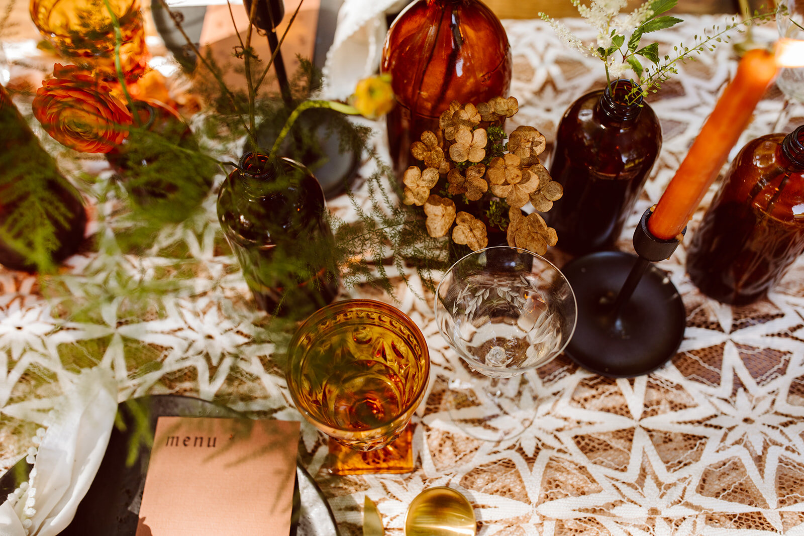 clusters of amber bud vases and rust taper candles on wedding tablescape