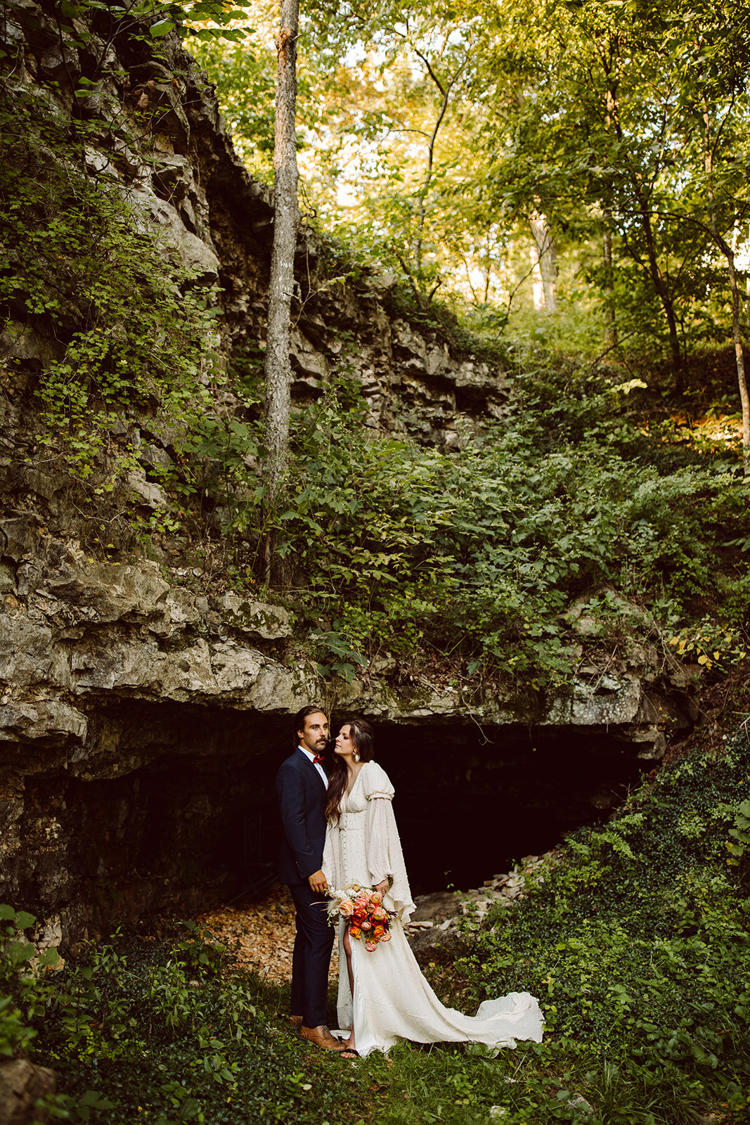 cave elopement with bright wedding bouqet