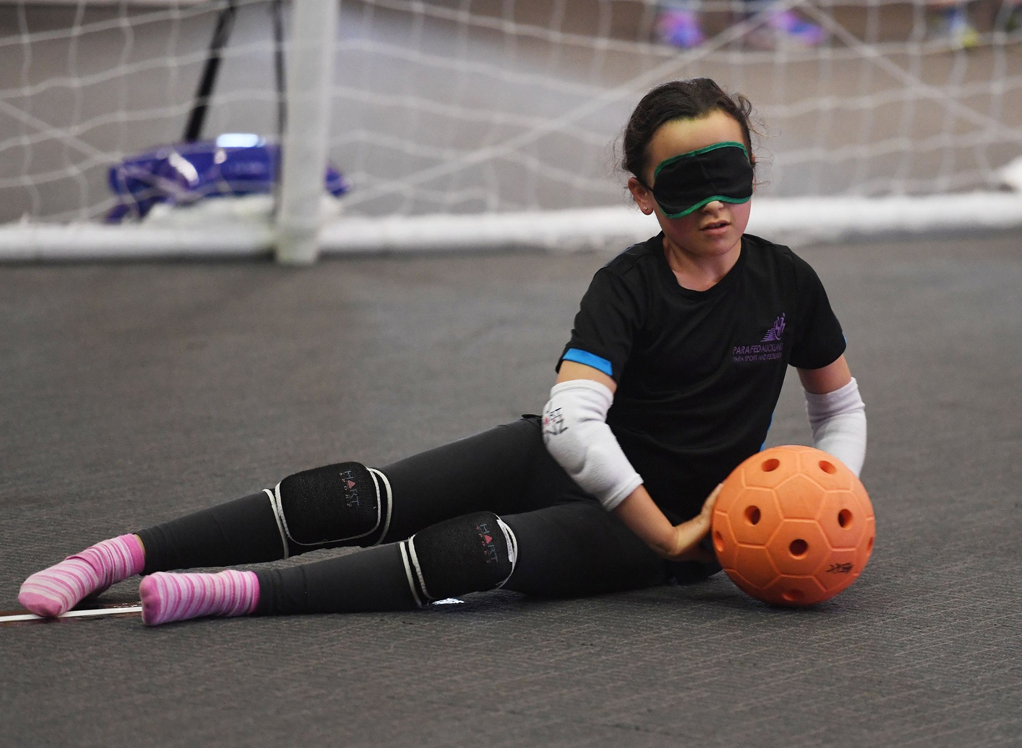 Young girl lying down in front of goalball goal to defend ball