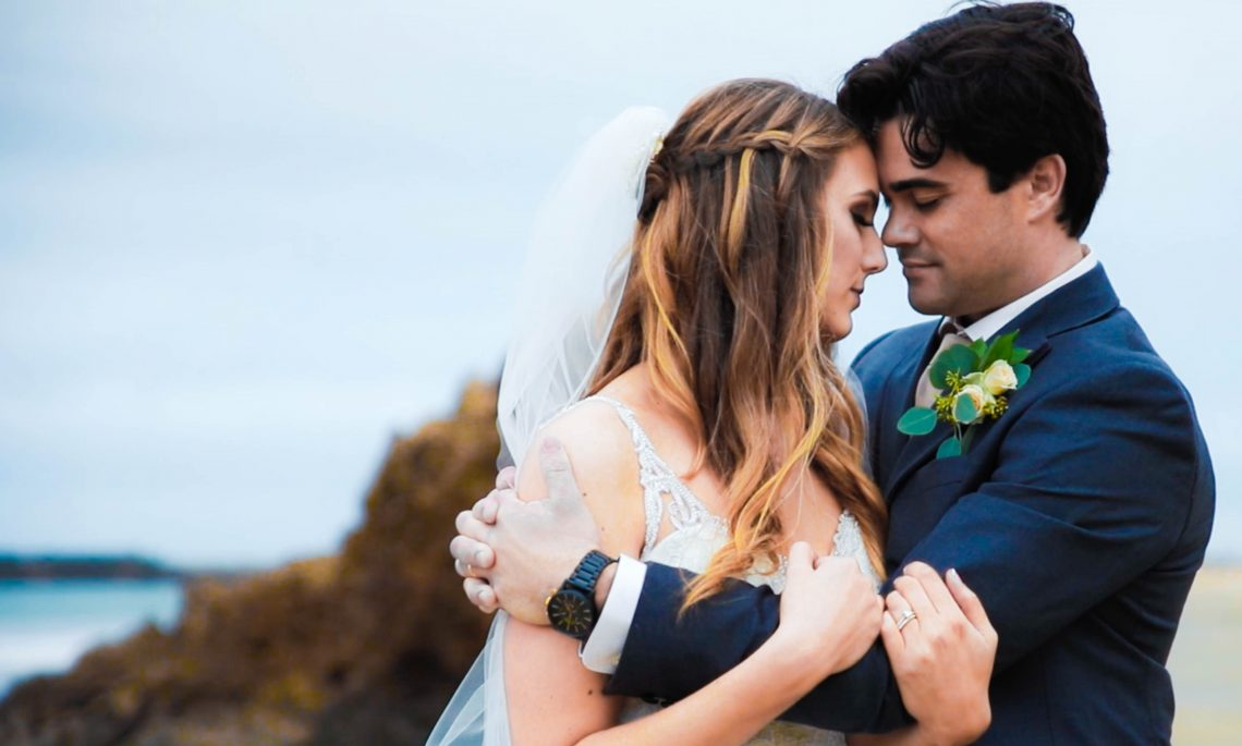 Wedding trends that age well - Bride and groom holding one another in front of the ocean.