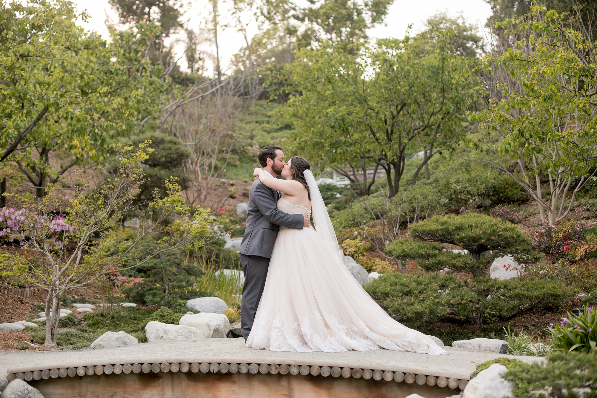 Wedding Photography Packages - San Diego, CA - Japanese Friendship Garden - Bride and groom kissing a small bridge overlooking the garden.