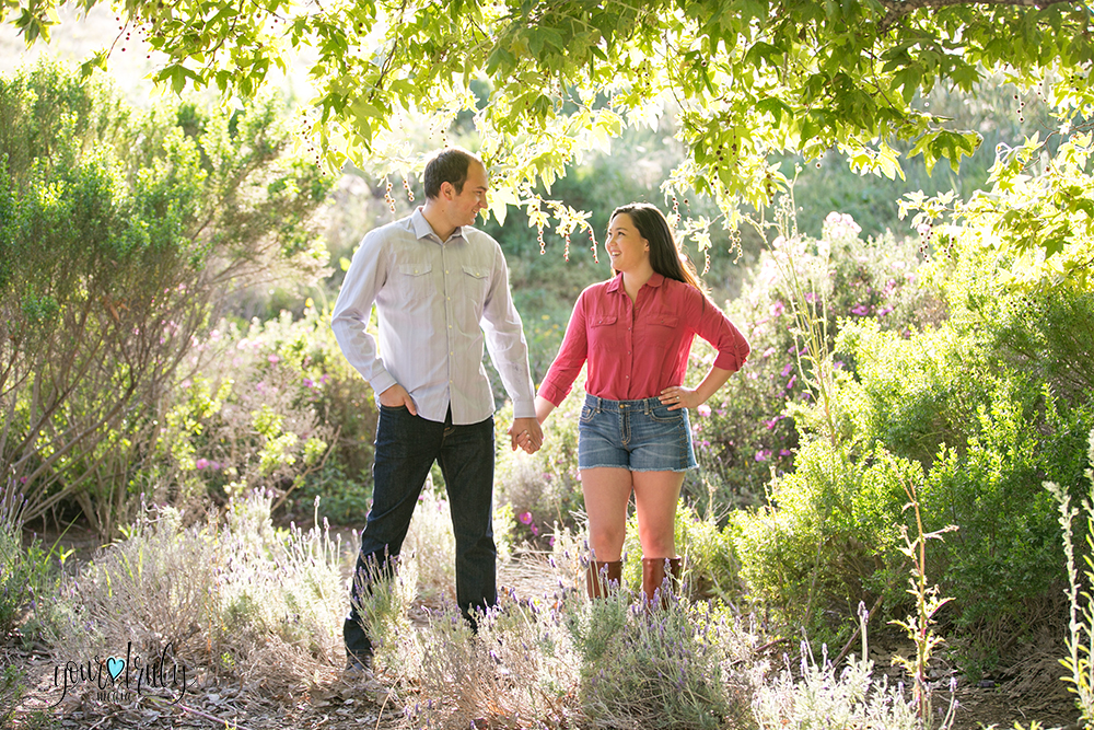 Engagement Photography Services, Orange County, CA - Engaged couple holding hands in a field of green.
