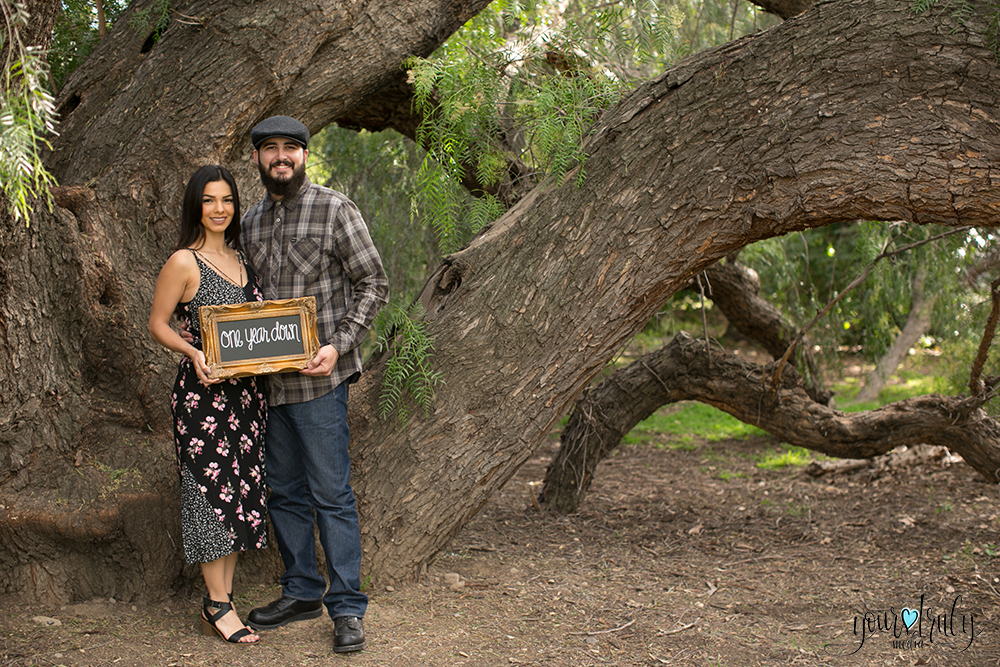 """1-year anniversary photography feature - Couple holding an anniversary sign. """"One year down."""""""
