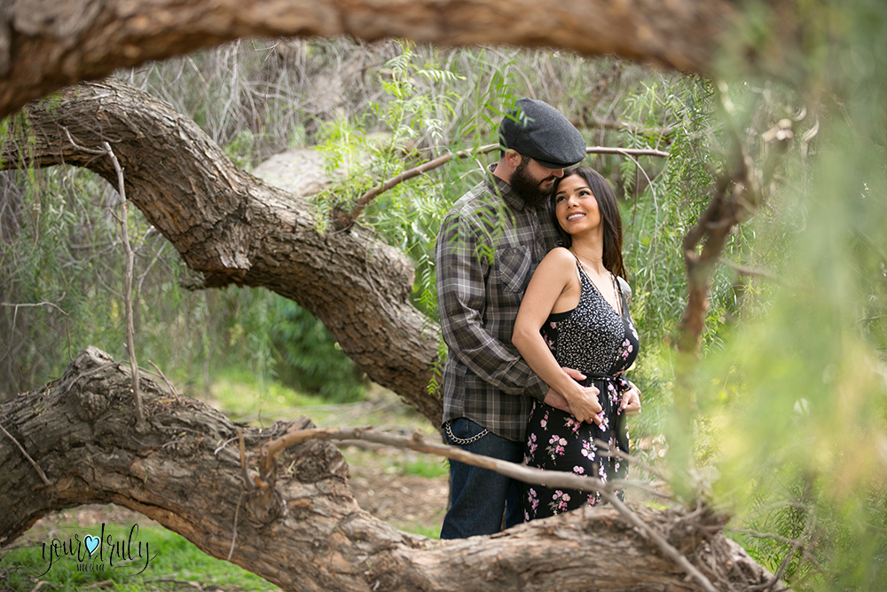1-year anniversary photography feature - Couple standing within the low hanging branches of a tree.