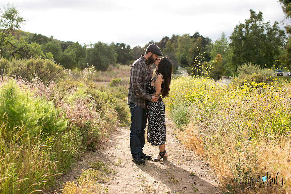 1-year anniversary photography feature - Couple kissing in a field of color.