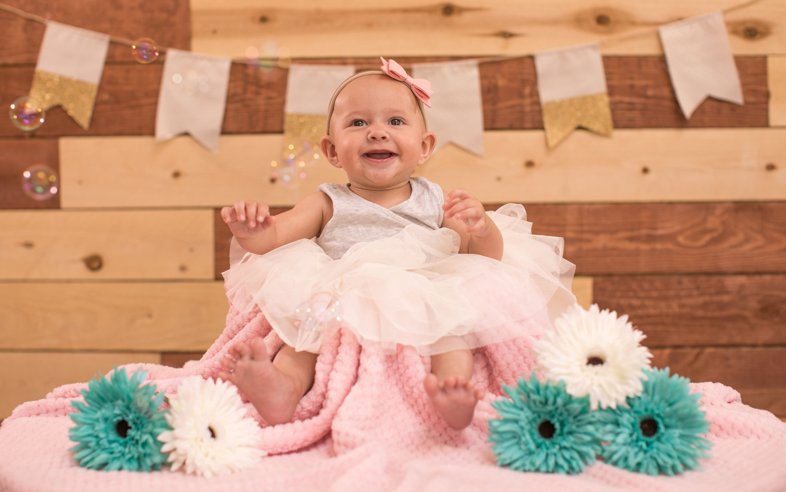 Orange County California Baby Photography Session - Baby girl smiling while sitting on a pink blanket.
