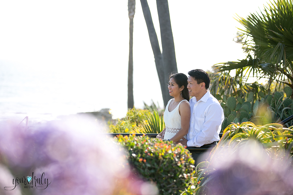 Engagement photography - Laguna Beach, CA - Engaged couple standing among a garden of bushes with the ocean in the background.