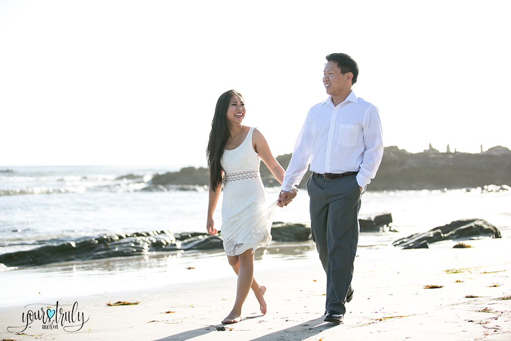 Engagement photography - Laguna Beach, CA - Engaged couple walking hand in hand along the beach.
