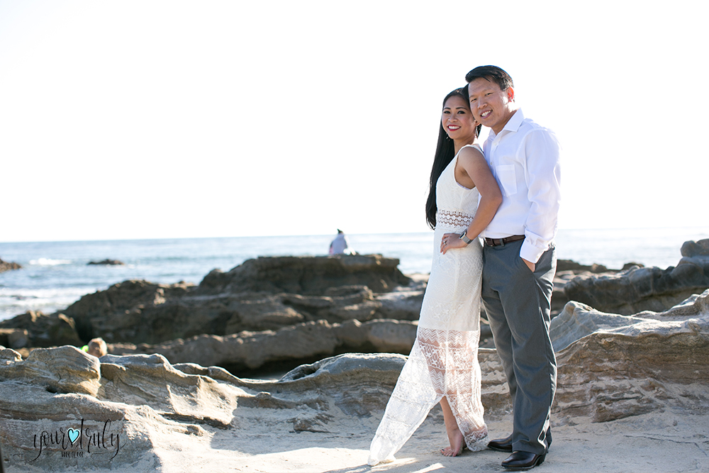Engagement photography - Laguna Beach, CA - Engaged couple standing in the stand in front of a rocky shoreline.