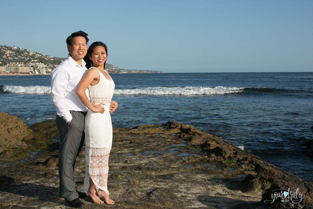 Engagement photography - Laguna Beach, CA - Engaged couple standing in front of the ocean as the waves crash towards the shore.