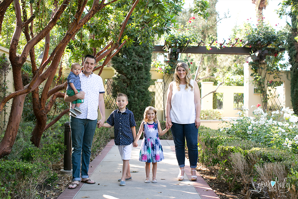 Family photography session - Orange County, CA - Scott family walking hand in hand along a sidewalk surrounded by flowers and trees.
