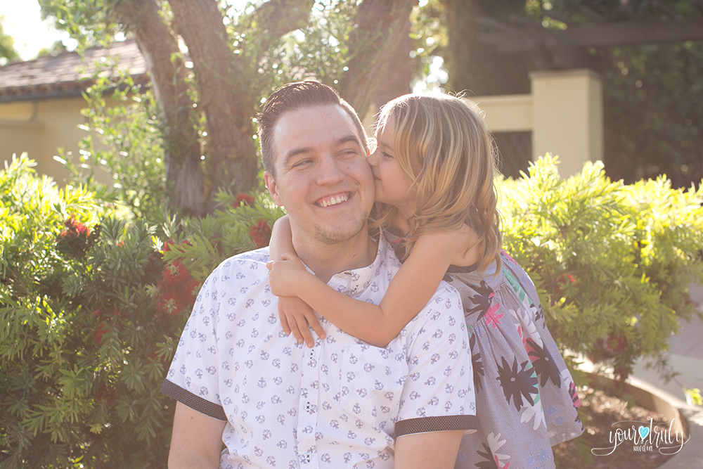 Family photography session - Orange County, CA - Daughter kisses her fathers cheek in a garden.